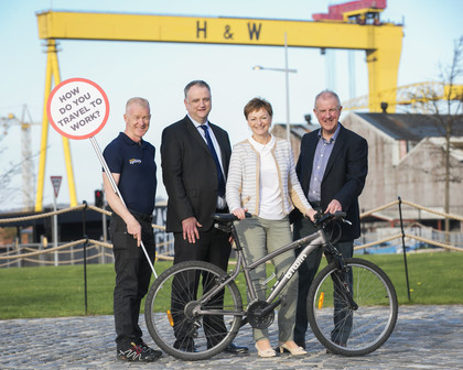 Three men and woman with bike and sign saying How do you travel to work with crane in background